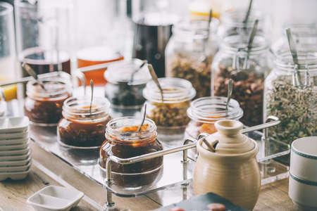 Glazen potten met zelfgemaakte jam, noten en granen. afgezwakt beeld Stockfoto
