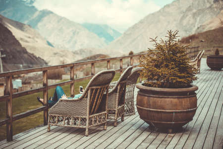 Girl sitting on terrace with beautiful mountain view. Toned image