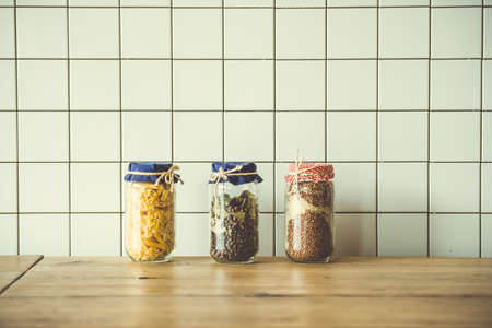 Jars with different grocery items on wooden kitchen table. Toned image Stock Photo