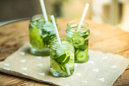 lemonade: Three retro glass jars of lemonade with cucumber and mint on wooden table Stock Photo