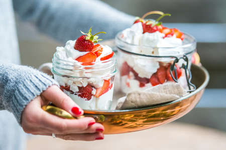 eton mess: Hands holding classic british summer dessert called Eton Mess. Strawberries, crushed meringue and whipped cream in jar