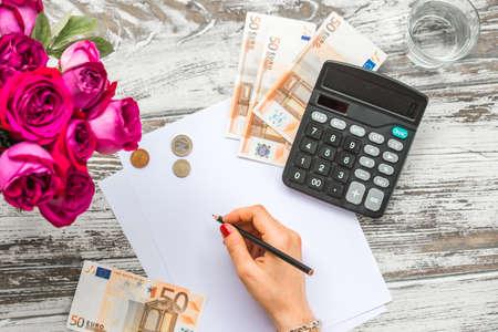 dinero euros: Mujer que cuenta el dinero del euro con la calculadora. Concepto de negocio. Vista superior Foto de archivo
