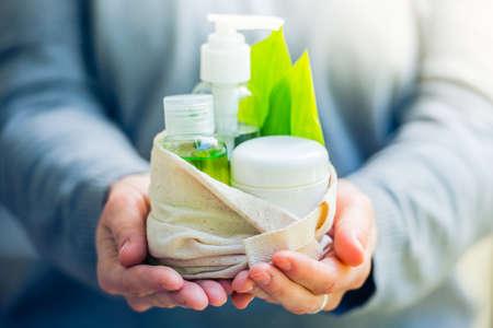 organic cotton: Bottiglia contenitore cosmetico con foglie di erbe verdi in piccolo sacchetto di cotone biologico in mani della donna