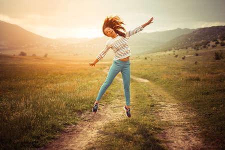 brincando: Hermosa niña saltando en el camino rural