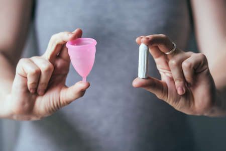 menstrual: Young woman hands holding different types of feminine hygiene products - menstrual cup and tampons