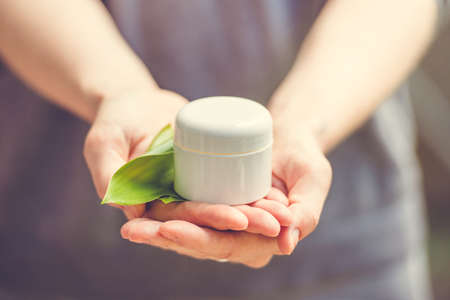 Cosmetic cream container with green herbal leaves in woman hands. Toned image Zdjęcie Seryjne - 41240452