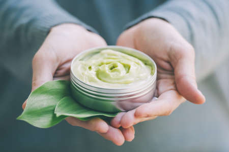 Cosmetic cream container with green herbal leaves in woman hands. Toned image Foto de archivo