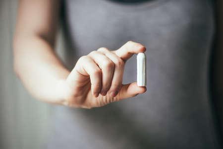 Junge Frau, die Hände, die hygienische tampon