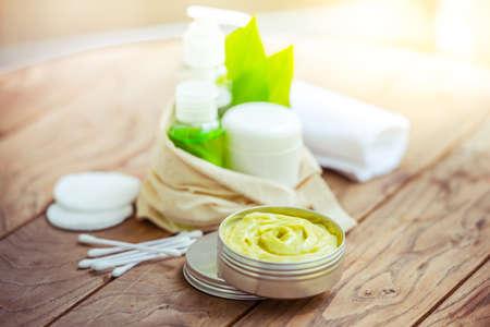 organic cotton: Bottiglia contenitore cosmetico con foglie di erbe verdi in piccolo sacchetto di cotone organico su fondo in legno