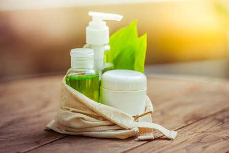 productos de belleza: Envase Botella cosmética con hojas de hierbas verdes en pequeña bolsa de algodón orgánico en el fondo de madera