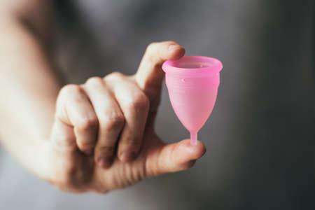 copa: Joven mujer mano sosteniendo copa menstrual