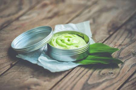 Récipient de crème cosmétique à base de plantes avec des feuilles vertes sur fond de bois Banque d'images - 41239051