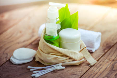 グリーン ハーブ化粧品ボトル容器は木製の背景の小さなオーガニック コットン バッグの葉します。