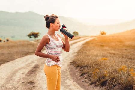 美しい少女の飲料水が屋外です。健康とスポーツのコンセプト 写真素材