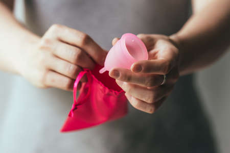 Young woman hands holding menstrual cup and small cotton bag