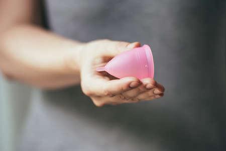 hemorragias: Joven mujer mano sosteniendo copa menstrual