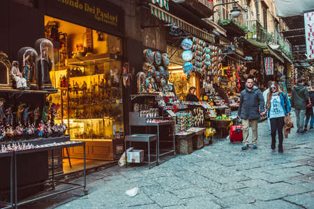 NAPLES, ITALY - MARCH 20, 2015: People walking through the old street  in the historical center of Naples, Italy. Naples is the the third-largest city in Italy with about 1 million residents Imagens - 41703733