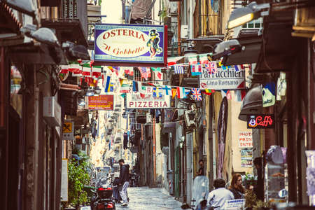 NAPLES, ITALY - MARCH 20, 2015: Small street with signs of restaurants, bars and cafes in Naples, Italy. Selective focus image 에디토리얼