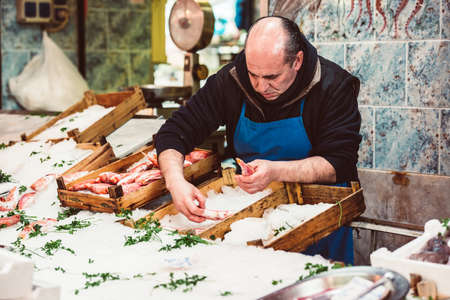 fish vendor: PALERMO, ITALY - MARCH 13, 2015: Vendor selling seafood and fish at famous local market Ballaro in Palermo, Italy