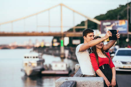 dnepr: KIEV (KYIV), UKRAINE - MAY 25, 2015: Young couple making selfie near bridge and the Dnepr (Dnieper) river in Kiev, Ukraine