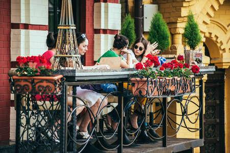 Kiew, Ukraine - 25. Mai, 2015: Junge Frauen im Chat und auf der Terrasse des kleinen Cafe in Kiew, Ukraine Essen