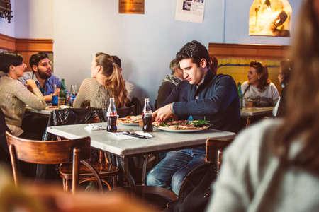 personas comiendo: NAPOLES, Italia - 20 de marzo 2015: La gente comiendo pizza en una pequeña cafetería y una pizzería en el centro histórico de Nápoles, Italia.