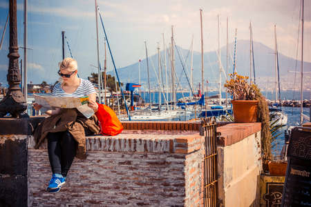 napoli: NAPLES, ITALY - MARCH 19, 2015: Tourist sitting with the map and mount and volcano Vesuvius as a background in the Gulf of Naples, Italy