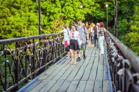 kyiv: KIEV (KYIV), UKRAINE - MAY 26, 2015: People walking on the lovers bridge in Mariinsky Park in Kiev, Ukraine