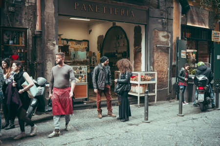 italy street: NAPLES, ITALY - MARCH 20, 2015: People walking through the old street  in the historical center of Naples, Italy. Toned picture