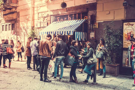 NAPLES, ITALY - MARCH 20, 2015: People standing and waiting near the famous pizzeria Gino Sorbillo in the historical center of Naples, Italy. Toned picture