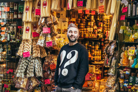 italy street: NAPLES, ITALY - MARCH 20, 2015: Vendor stands near grocery shop with classical italian food in the old center of Naples, Italy.