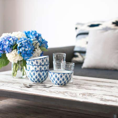 hortensia 꽃과 유리의 꽃다발 현대 나무 커피 테이블과 베개와 아늑한 소파에 그릇. 거실 인테리어 및 홈 인테리어 개념