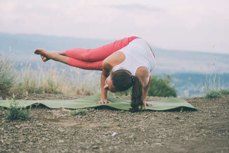 yoga: Young woman practicing yoga outdoor in the nature with city on background. Toned image