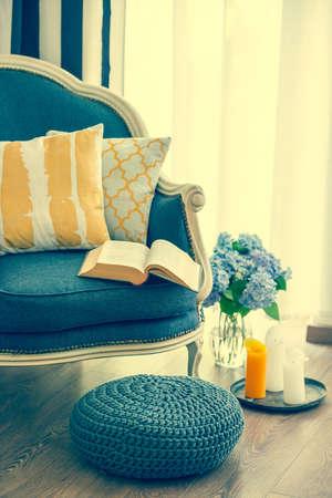 Gemütliche Sessel mit offenen Buch und dekorativen Kissen. Interieur und Wohnkultur Konzept. Getönt Lizenzfreie Bilder