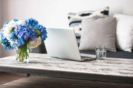 モダンな木製コーヒー テーブル、ラップトップ、枕と居心地の良いソファ。リビング ルームのインテリアや家庭のインテリア コンセプト