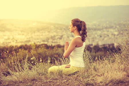 Young woman sits in yoga pose with city on background. Freedom concept. Calmness and relax, woman happiness. Toned image Stockfoto