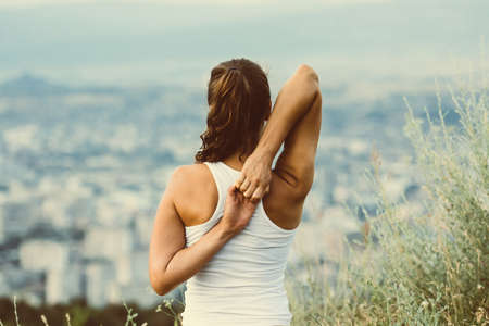 Young woman sits in yoga pose with city on background. Freedom concept. Calmness and relax, woman happiness. Toned image 스톡 콘텐츠