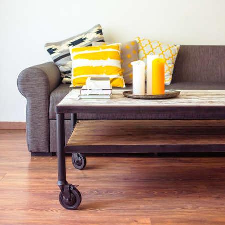 현대 나무 커피 테이블과 베개와 아늑한 소파. 거실 인테리어와 홈 인테리어 개념