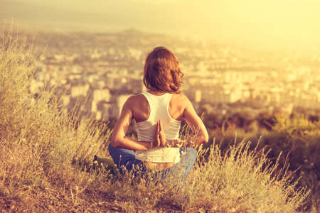 Young woman sits in namaste yoga pose with city on background. Freedom concept. Calmness and relax, woman happiness. Toned image