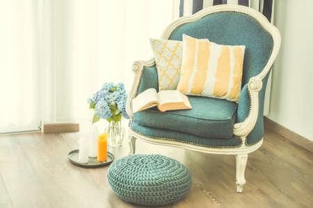 開いた本と装飾的な枕と居心地の良いアームチェア。インテリア、家の装飾の概念。トーンのイメージ