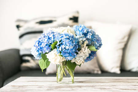 Bouquet of hortensia flowers on modern wooden coffee table and cozy sofa with pillows. Living room interior and home decor concept Foto de archivo