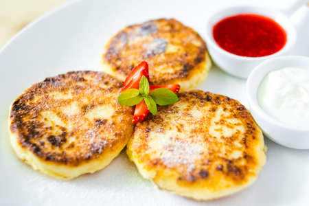 cottage cheese: Cottage cheese pancakes with sour cream and strawberry sauce Stock Photo