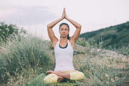 back roads: Young woman sits in yoga pose with city on background. Freedom concept. Calmness and relax, woman happiness. Toned image Stock Photo