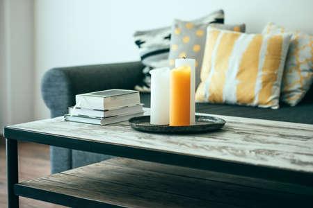 モダンな木製コーヒー テーブルと枕と居心地の良いソファ。リビング ルームのインテリアや家庭のインテリアのコンセプト。トーンのイメージ