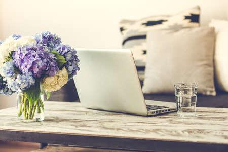 trabajando en casa: Mesa moderna de madera caf�, port�til y c�modo sof� con almohadas. Sala de estar interior y el concepto de la decoraci�n del hogar. Imagen entonada