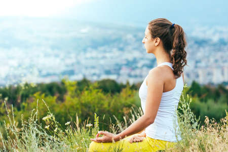 Young woman sits in yoga pose with city on background. Freedom concept. Calmness and relax, woman happiness.