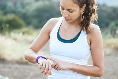 salud y deporte: Mujer que usa la actividad de seguimiento. concepto de fitness al aire libre