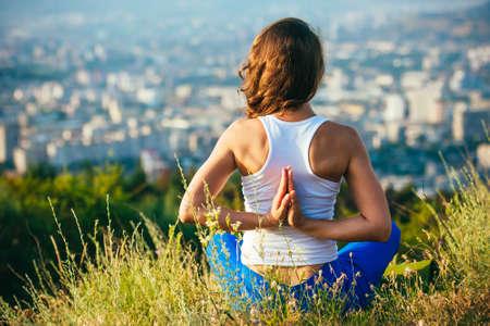 libertad: La mujer joven se sienta en namaste yoga plantean con la ciudad en el fondo. Concepto de la libertad. La calma y la tranquilidad, la felicidad mujer.