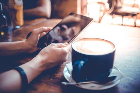 Grote kop koffie en handen die tablet in cafe. Getinte afbeelding Stockfoto