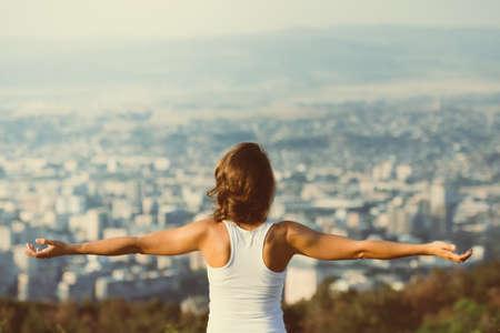 libertad: J�venes manos mujer difusi�n amplia abren con la ciudad en el fondo. Concepto de la libertad. El amor y las emociones, mujer felicidad. Imagen entonada Foto de archivo